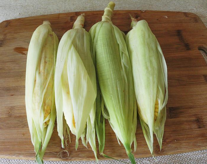 Husks pulled back over the seasoned corn