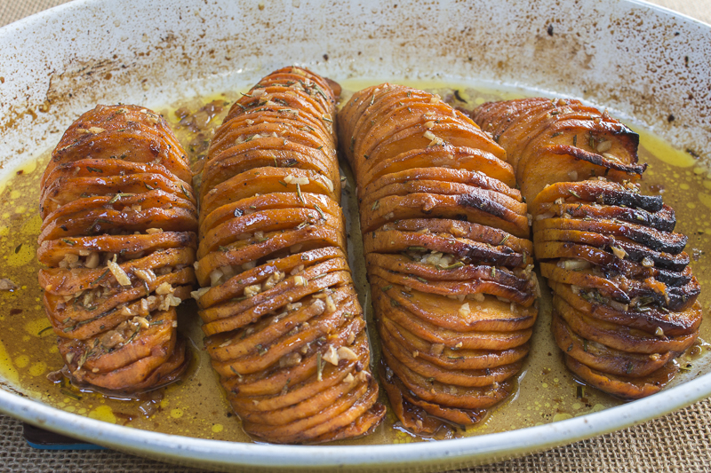 The potatoes will fan out beautifully, Stuff with garlic, top with rosemary and baste with maple glaze