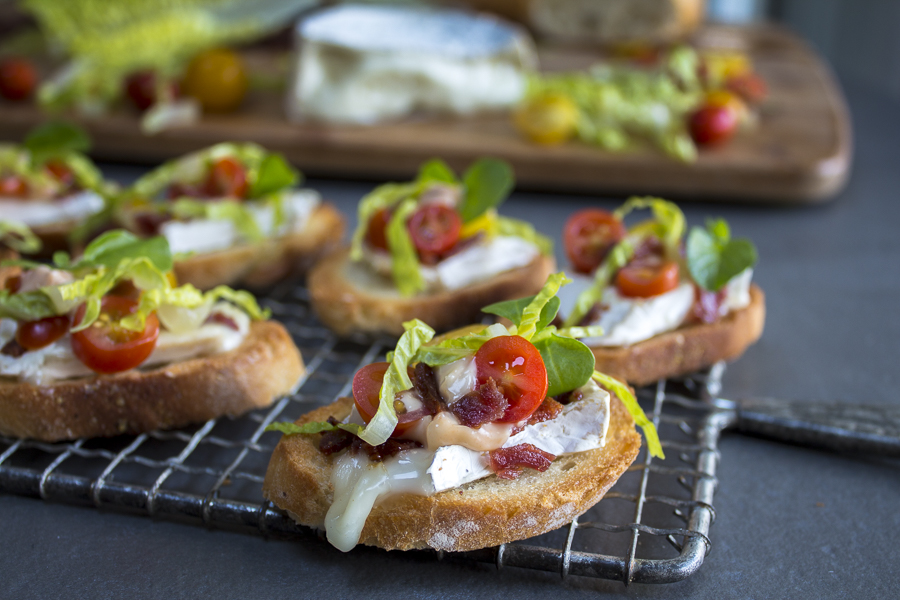 The ultimate healthy appetizer - a crisp garlicky baguette slice covered with oozing brie cheese, bacon, lettuce, tomato and a touch of spiked mayo