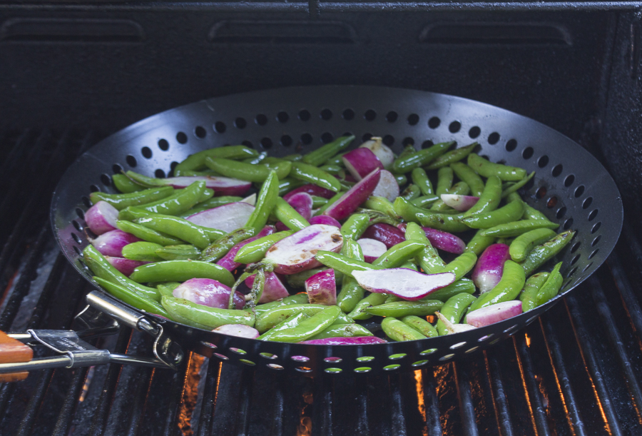 A grill basket with the veggies on top of the grates of the grill - imparts a nice smoky flavor