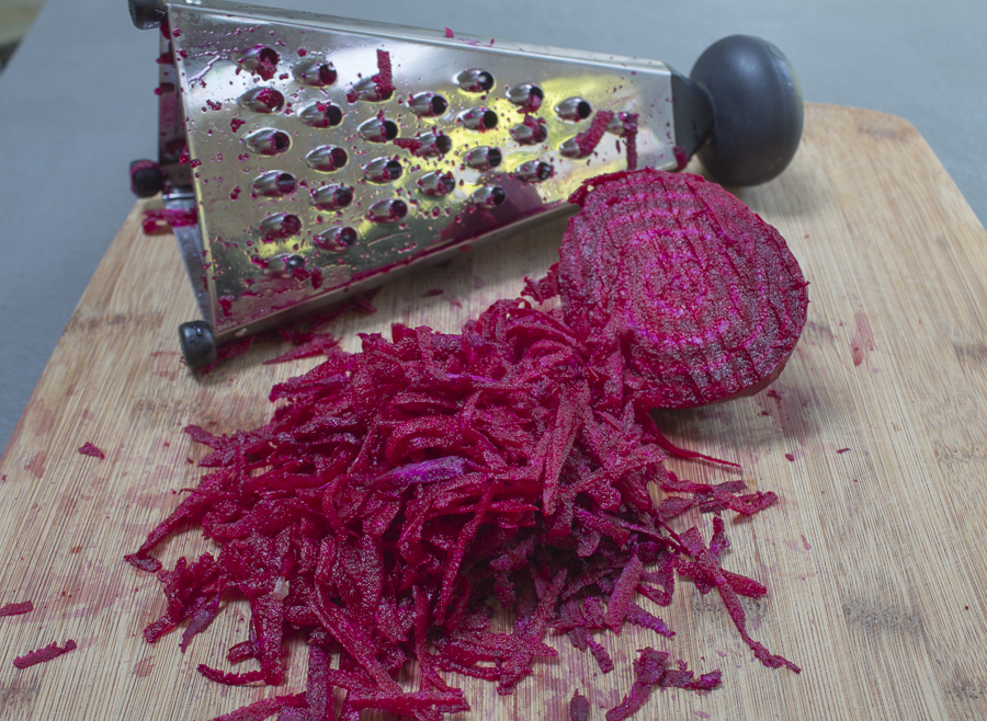 Peel a fresh ruby beet, then simply grate it, and squeeze dry
