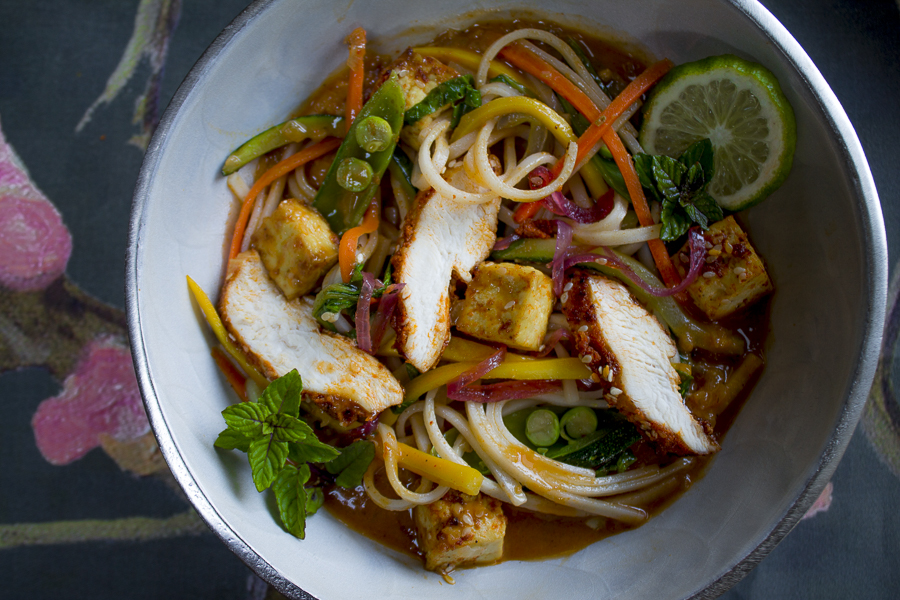 A wonderful noodle bowl! With a luscious sauce,  vegetables,  sesame tofu and roasted slices of chicken. Don't forget to garnish with flavorful mint leaves!